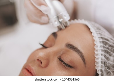 Cropped close up of a beautiful woman getting facial treatment at beauty clinic. Cosmetologist using hardware skincare equipment. Beautician performing microcurrent therapy on female patient