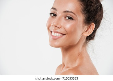 Cropped close up beauty portrait of a smiling pretty woman with soft healthy skin looking at camera and laughing isolated over white background