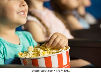 Cropped close up of a cute little boy smiling grabbing popcorn from the bucket while watching a movie at the cinema copyspace eating eat food snack junk tasty delicious children kids nutrition health