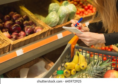 Cropped close up of a female customer checking her shopping list while walking with a trolley through supermarket copyspace people lifestyle buying consumerism shopper buyer retail selling sale