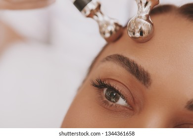 Cropped close up of a female patient receiving microcurrent facial skin treatment at beautician office. Selective focus on beautiful woman eye, receiving face care therapy. Hardware cosmetology