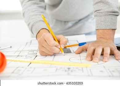 Cropped close up of hands of a male architect drawing on blueprints designing architectural project sketching building plan development future urbanization engineer profession creating construction