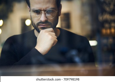 Cropped close up image of pensive bearded entrepreneur in optical spectacles for better views dressed in black sweatshirt.Pondering businessman in trendy eyeglasses thinking on blurred background