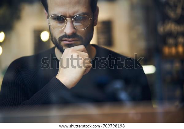 Nahaufnahmen von pensionierten bärtigen Unternehmern in optischen Brillen für bessere Ausblicke in schwarzem Sweatshirt.Erstaunlicher Geschäftsmann in trendigen Brillen auf unscharfem Hintergrund