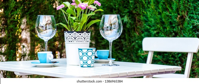 Cropped close up image table setting with a wine glasses, cups and flowers in a pot outdoors in yard of country home, rustic simple charming style, dinning, cozy atmosphere, beautiful fine elements