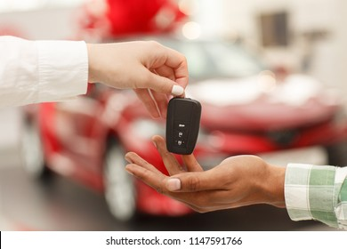 Cropped close up of a male customer receiving car keys from salesperson after buying new automobile at the dealership salon. Car dealer handing key to male customer. Buying car, selling cars concept