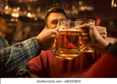 Cropped close up of men clinking beer glasses toasting drinking beer at the pub together enjoyment recreation relaxing party event mood celebration festive people friends friendship together brewery