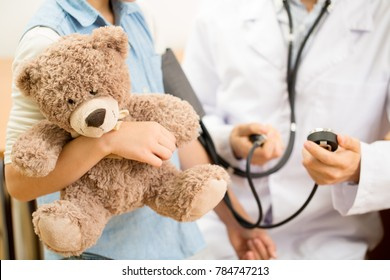 Cropped close up of a pediatrician doctor measuring blood pressure of his young patient girl hugging her teddy bear during medical examination at the hospital copyspace healthcare medicine kids