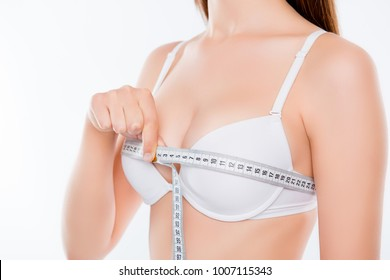Cropped close up photo of beautiful attractive slim thin skinny with smooth skin woman's body, hand measuring breast, isolated on white background, wellbeing, wellness concept