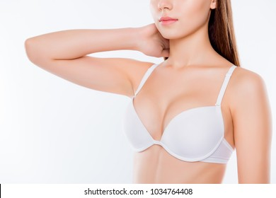 Cropped close up photo of beautiful woman's breast clothed in white classic bra cups she is touching neck skinny slender slim body flawless skin isolated on white background