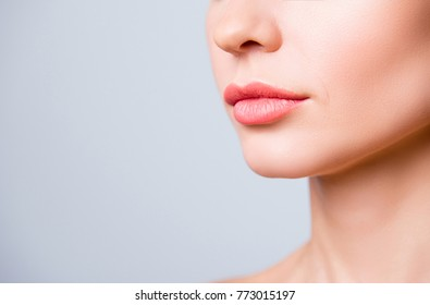 Cropped close up photo of beautiful woman's lips with shape correction, isolated on grey background, copyspace