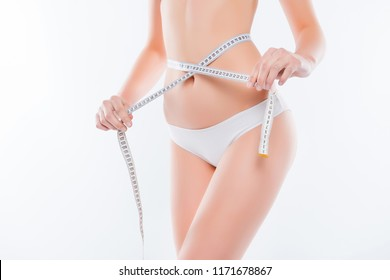 Cropped close up photo of fatless slender body parts and proportions woman's hands holding white centimeter measuring waistline isolated on background