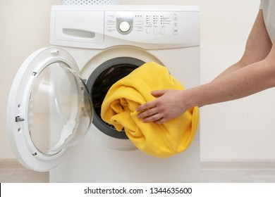 Cropped and close up photo of preparation for laundry process. Woman putting clothes in white washing machine and standing inside bright apartment light interior