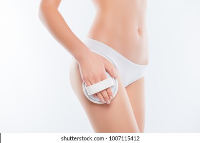 Cropped close up photo of sexy thin slim pure clean clear skinny woman's hips and legs wearing white classic underlinin underclothes, she is using brush for massaging body isolated on background