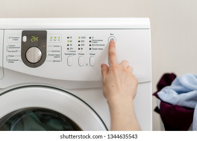 Cropped and close up photo of woman hand switch laundry cycle on washing machine inside flat with bright interior