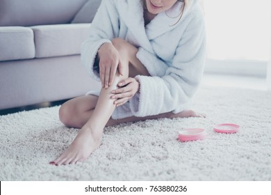 Cropped close up photo of woman wearing white bathrobe, she is sitting on the floor and applying moisturizing cream on her legs and nails after depilation and taking a shower