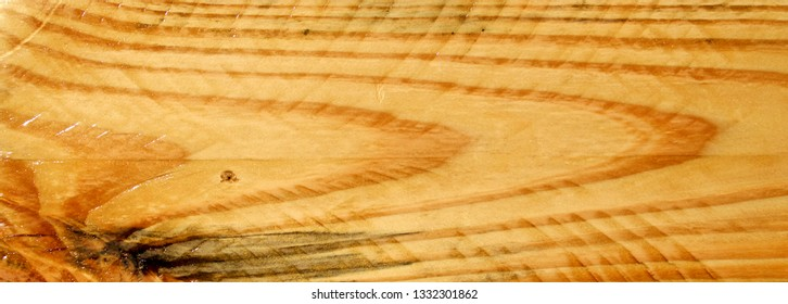 Cropped close up of Polyurethaned plain pine plank board showing grain and saw marks.