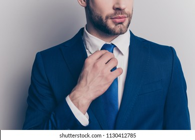 Cropped close up portrait with half face of virile, harsh, stunning man correcting his tie with arm, wearing blue suit, isolated on grey background
