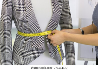 Cropped close up of a professional fashion designer using measuring tape while working at her showroom making measurements on a mannequin profession occupation career style business atelier tailoring