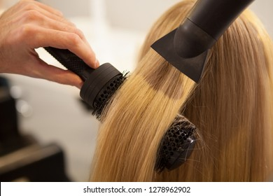 Cropped close up of a professional hairdresser using round brush and blow dryer, styling long blond hair of his female client. Healthy strong hair of a woman during new hairstyle treatment, copy space