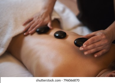 Cropped close up of a professional therapist masseuse doing hot stones massage her female client service relaxation therapy treatment healthy spa wellbeing wellness recreation hotel resort