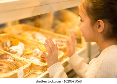 Cropped close up profile shot of a little girl examining showcase full of desserts croissants pastries at the local bakery copyspace hunger eating food consumerism purchasing consumptions buying shop