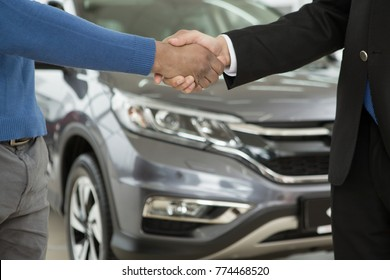 Cropped close up of a salesman shaking hands with his male African client after selling a new car buying buyer consumerism customer client service deal agreement contract partnership sales discount