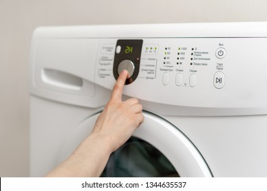Cropped close up and side view photo of woman press button on white washing machine. She choosing laundry setting standing inside light flat interior