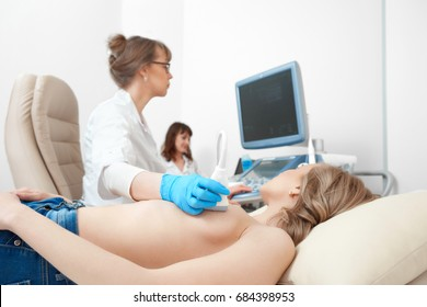 Cropped close up of a topless woman getting breast sonogram at the gynecological clinic health feminine cancer awareness concept.