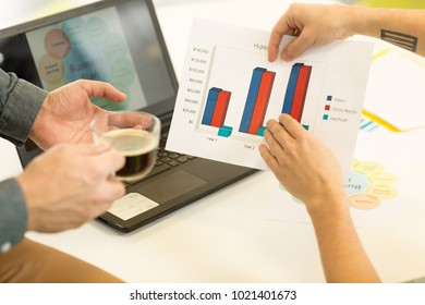 Cropped close up of two businessmen examining colorful graphics and diagrams working at the office laptop on the background team teamwork partnership development analysis strategy planning.