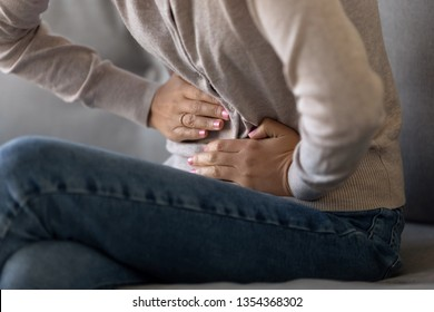 Cropped close up view girl touch stomach suffers from severe ache sitting on sofa, twinges of pain caused by menstrual period, gastric ulcer, appendicitis or disease of gastrointestinal system concept