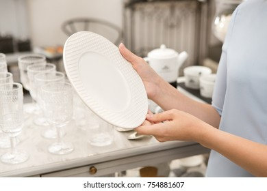 Cropped close up of a woman holding ceramic plate shopping for dinnerware at the store copyspace housewares dish luxury lifestyle home decor interior design shopper consumerism purchase retail sales