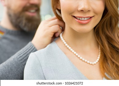 Cropped close up of a woman smiling her husband helping her trying on a pearl necklace fashion style luxury lifestyle love affection gift present consumerism anniversary romance romantic relationships