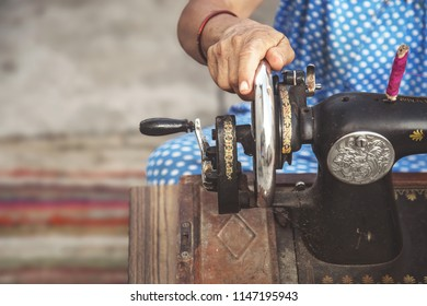 Cropped close up of a woman using sewing machine