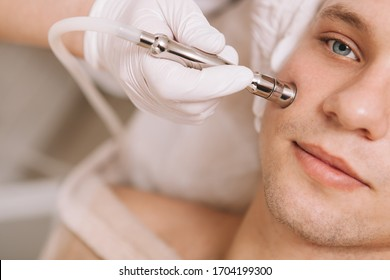 Cropped close up of a young man having facial hardware skincare treatment by professional dermatologist