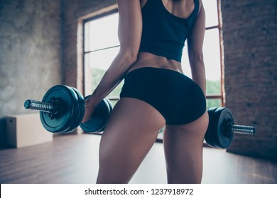 Cropped close-up bottom of pretty attractive beautiful strong sporty sportive slim lady wearing sports top and panties holding keeping lifting two dumbbells house domestic class studio work out