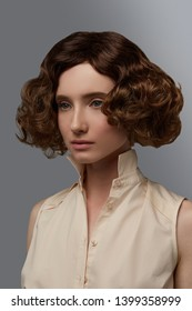 Cropped closeup half-turn view shot of girl with chestnut curly blunt bob hairstyle, wearing sleeveless shirt with standup collar. The lady with black flicks is posing against the gray background.
