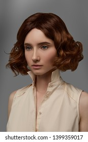 Cropped closeup half-turn view shot of girl with reddish brown blunt bob hairstyle, wearing beige sleeveless shirt with standup collar. The lady with black flicks is posing against gray background.