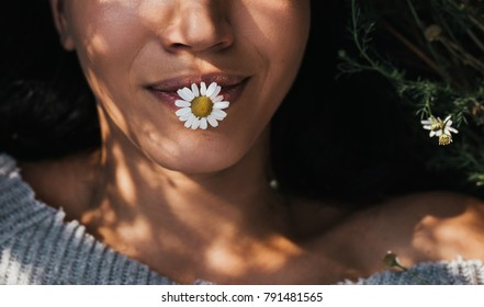 Cropped close-up horizontal shot of brunette young girl with daisy flower in mouth outdoors enjoying nature. Portrait of an attractive Caucasian woman feel free with copy space. Cover idea mood