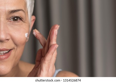Cropped closeup image of gorgeous natural mature woman applying nourishing face cream and taking care of her skin, Facial skin care for women over 50 concept, Space for text
