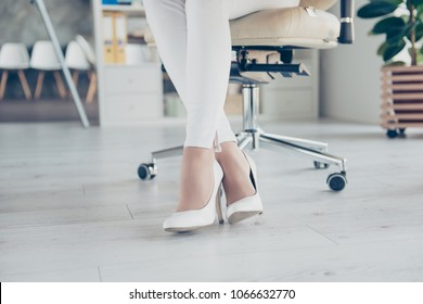 Cropped closeup photo of charming beautiful slim attractive sexual romantic woman' legs wearing white tight classic trousers sitting on luxurious beige armchair on wooden light gray parquet