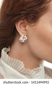 Cropped closeup portrait of girl with brown hair, wearing blouse with ruffles, posing on white background. The lady is wearing massive earrings, adorned with crystals and snowy floral application.