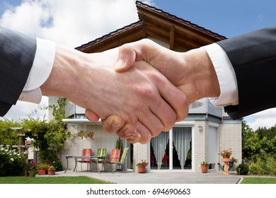 Cropped closeup of realtor shaking hands with client after selling house