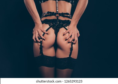 Cropped close-up rear back behind view of perfect sporty shape gorgeous attractive thin fit slim lady in swordbelt holding gluteal muscles teasing isolated over dark black background