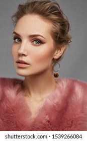 Cropped close-up shot of a brown-haired lady in pink furs wearing stud earrings in the form of the brown fur balls with leopard spots fixed on the golden ring.