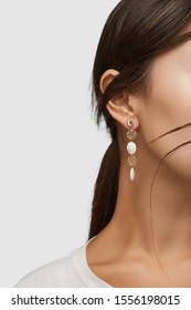Cropped close-up shot of a brunette woman in an ivory white top and with a stud earring made as a string of golden wire balls and nacre gem pellets.