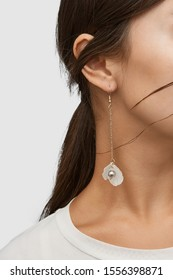 Cropped close-up shot of a brunette woman in an ivory white top and with a hook earring with long golden chain and dangling nacre seashells and a silver shimmering pearl.
