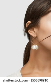 Cropped close-up shot of a brunette woman in an ivory white top and with a stud earring with a golden rhombus frame with dangling nacre seashells.