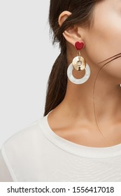 Cropped close-up shot of a brunette woman in an ivory white top and with a stud earring made as a red gem heart-shaped base with dangling wavy golden disk and a white nacre holed circle.