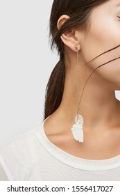 Cropped close-up shot of a brunette woman in an ivory white top and with a stud earring with long golden chains with dangling white fabric feather and nacre disc.